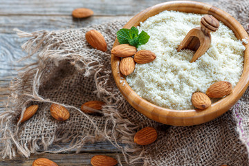 Almonds, mint and almond flour in a wooden bowl.