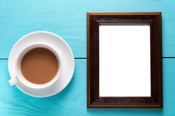 empty photo frames on wooden table with cup of tea.
