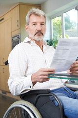 Frustrated Man In Wheelchair Reading Letter