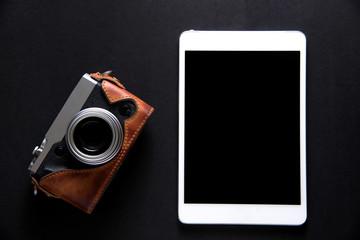 tablet with vintage camera on black background