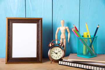 Empty photo frame with office supplies objects