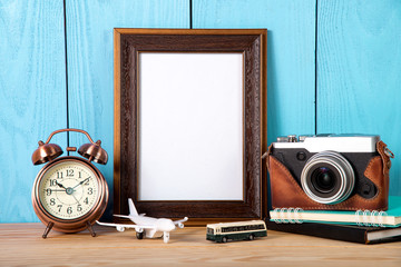 Travel gear and empty photo frame on blue wooden background.