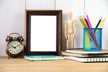 Empty photo frame with office supplies objects on wood table