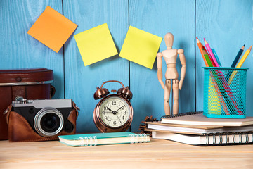 office supplies objects and camera on wood table