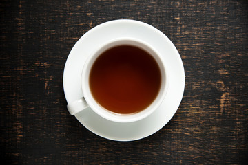 Cup of tea on dark wooden background, top view