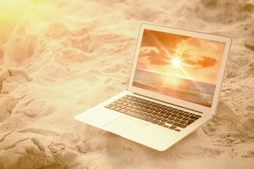 Composite image of laptop kept on sand at beach