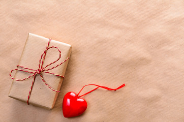 Heart with handmade gift box wrapped with craft paper and red bow for Valentine's day