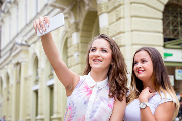 two girlfriends taking selfie photo with mobile phone