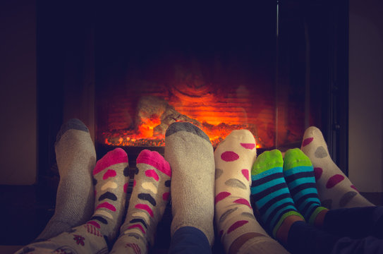 Feet in socks of all the family relaxing and warming by cozy fire