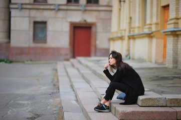 Young pretty brunette girl in a black cardigan and trousers thoughtfully sitting on the steps of porch near city building.