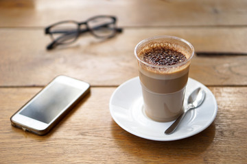 View of a wooden table with hot coffee, smartphone and glasses on it - Wooden background - focus on a cup of coffee