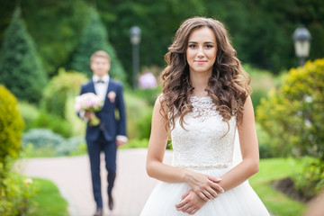 Beautiful young bride standing on lane in summer park, groom with bouquet in background