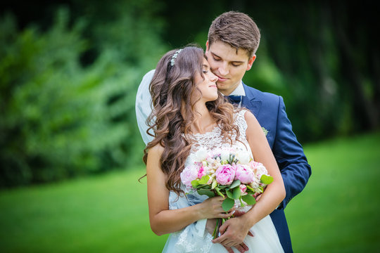 Beautiful young bride and groom in park