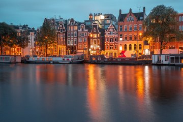Canvas Prints Textures Amsterdam canal Amstel with typical dutch houses and boats during twilight blue hour, Holland, Netherlands.