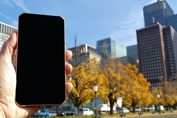 blank black screen of smartphone with the background of modern office building