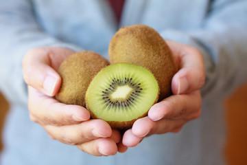 holding fresh kiwi fruit