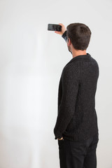Ein junger Mann macht ein Selbstportrait mit seinem Smartphone