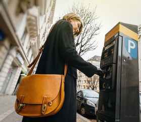 Woman paying for the parking at the teller machine in the city