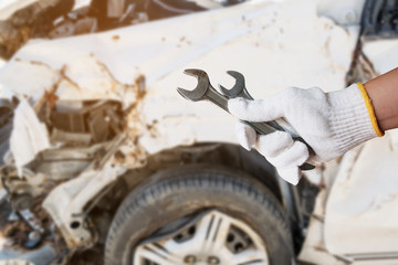 hand hold wrench with car crash damage background