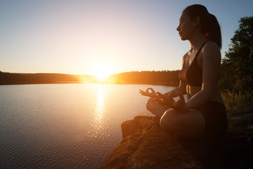 Young healthy woman is practicing yoga at mountain lake during s