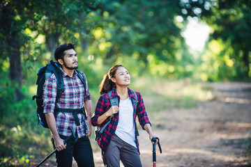 Young couple walking with backpacks in forest. Adventure hikes,