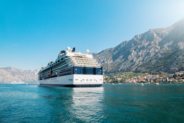 Wall Mural - Cruise liner ship swimming at blue adriatic sea, mountains landscape