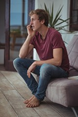 Man sitting on sofa and talking on mobile phone