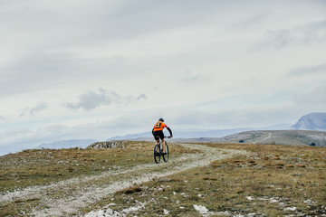 male cyclist with a backpack on mountainbike rides on a mountain trail