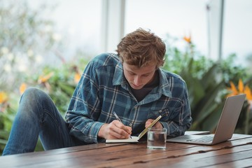 Man writing notes on diary at home