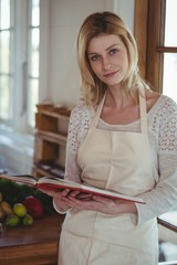 Portrait of beautiful woman holding recipe book in kitchen