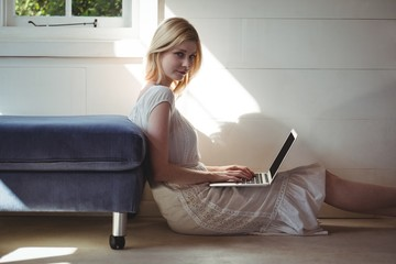 Portrait of beautiful woman using laptop in living room