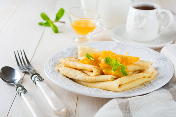 Thin crepes with orange citrus sauce for breakfast on light background. Selective focus.