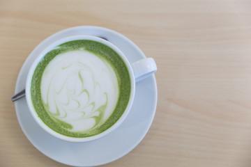 hot latte green tea on wood table