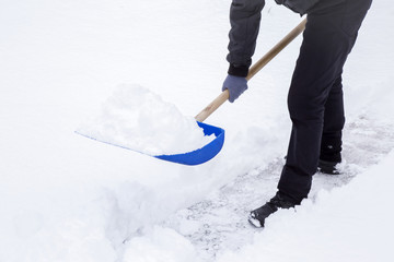Man cleaning snow with shovel in winter day.