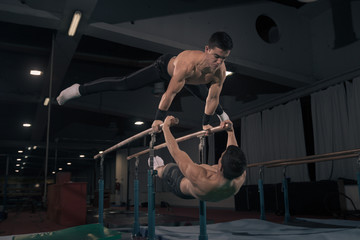 Two men gymnast in air, parallel bars