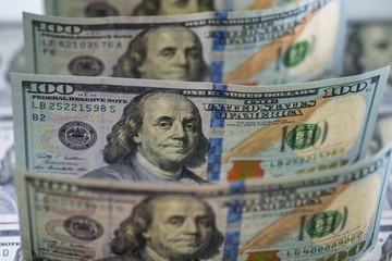 Row of hundred us dollar bills. Backlight, watermarks are visible. Selective focus. Bills are standing on hundred us banknotes background. Close up image.