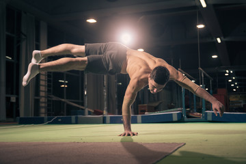 Foto op Aluminium Gymnastiek Young man gymnast, one hand cartwheel