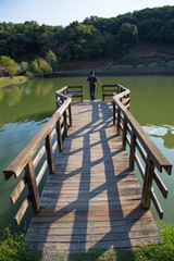 Rear View Of Man Standing On The Edge Of Wooden Pier Looking At The Calm Lake At Sunny Autumn Day