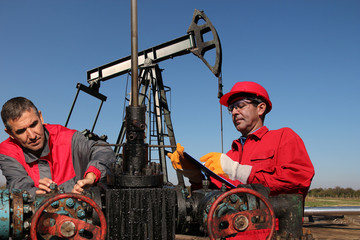 Engineers Inspecting Oil Field Equipment / Engineers monitoring oil pumping unit at a oil field