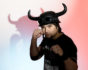 silhouette Rocker man in a horned helmet posing on red background