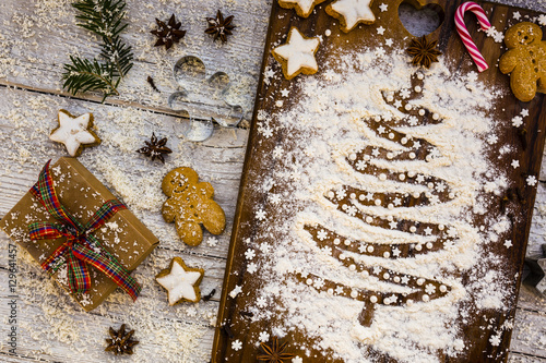 Christmas baking, decorations on cakes and cookies on wooden background.