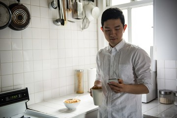 Man using mobilephone while having a cup of coffee at home