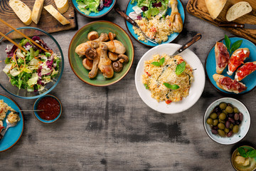 Risotto, roasted chicken legs and snacks on a wooden table