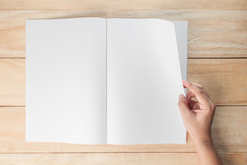 hand open blank book or magazines, book mock up on wood background