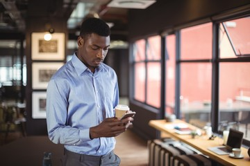 Businessman holding disposable coffee cup and using mobile phone