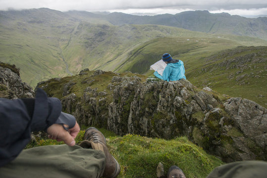 A woman checks her map while looking towards Great Langdale valley from the Langdale Pikes, Lake District National Park, Cumbria