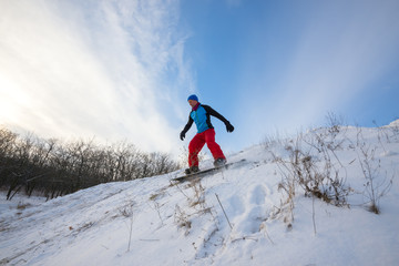 Snowboarder is riding in winter forest. Wide angle