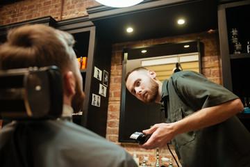Young man getting beard haircut in barbershop