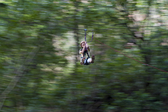 A girl clings on and laughs with delight on a zip line, Nepal