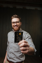 Man in eyeglasses showing credit card on camera